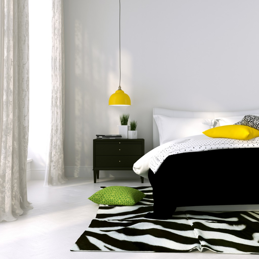 Bedroom in black and white with the yellow lamp and colored cushions
