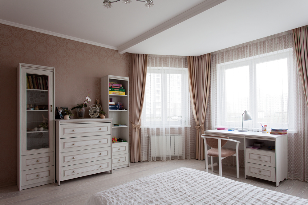 White chest of drawers, bad and a writing desk near the window in a room